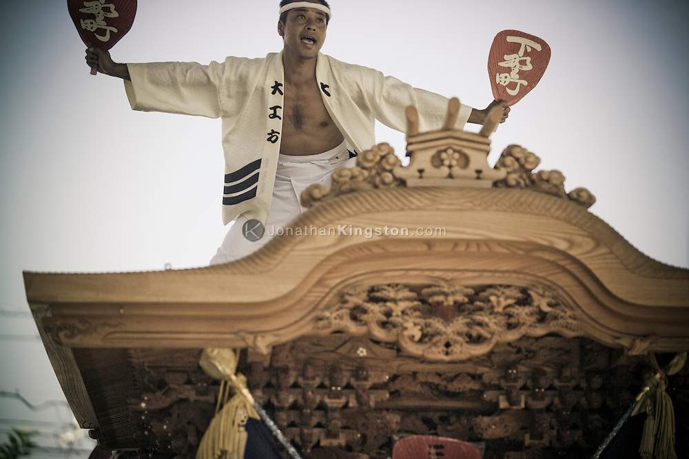 A guild leader rides on top of the Danjiri during the  Kishiwada Danjiri Matsuri festival in Osaka, Japan.  The Kishiwada Danjiri Matsuri festival is one of the most famous Danjiri Matsuri's in Japan and attracts thousands of tourists every year.  Danjiri are large wooden carts, weighing as much as four tons, in the shape of a shrine or temple and it is believed that spirits or gods reside in the Danjiri.  In Kishiwada, Osaka, the carts are pulled thru the streets of the city on the festival day by teams of town guild members up to 1000 strong wearing their guild happi coat and headband.  The guild leader rides on top of the Danjiri cart hopping and dancing as the danjiri moves faster and faster.