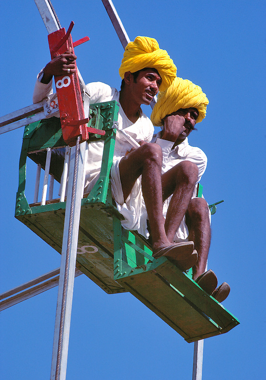 The men on the Ferris Wheel can see all of the grounds of the Pushkar Fair, Rajasthan, India.