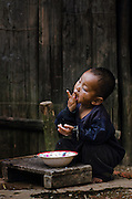 A boy enjoys his meal in a mountain village near Luang Prabang, Laos.