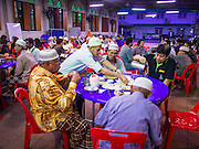 16 JULY 2013 - BANGKOK, THAILAND:  People at Iftar, the Muslim meal that breaks the day long Ramadan fast, at Jami Ul Khoy Riyah Mosque in the Ban Krua section of Bangkok. Ban Krua is the oldest Muslim section of Bangkok. It was established during the reign of Rama I, the first King of the Chakri dynasty. He enlisted Cham Muslims in what is now Cambodia to fight on the Siamese (Thai) side of war between the Khmers and Siamese. He rewarded their service with a grant of land that is now Ban Krua.         PHOTO BY JACK KURTZ