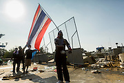 02 DECEMBER 2013 - BANGKOK, THAILAND:  Anti-government protestors wave a Thai flag at a police barricade during a riot in Bangkok Monday. Anti-government protestors and Thai police continued to face off Monday for a second day. Police used tear gas, water cannons and rubber bullets against protestors who charged their positions near the barriers on Chamai Maruchet bridge on Phitsanulok Road, which leads to the Government House.    PHOTO BY JACK KURTZ