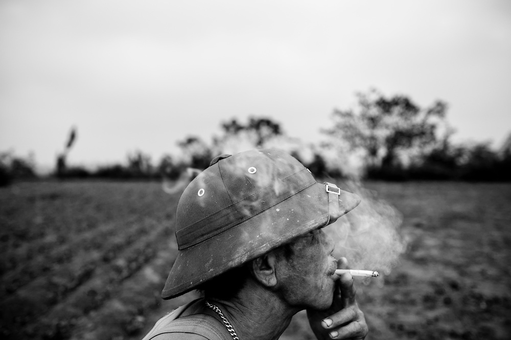 Farmer Nguyen Van Duoc stops for a cigarette on his field beneath Long Bien Bridge in Hanoi, Vietnam. Each harvest he grows over 200 pounds of soybeans to sell to tofu makers in the city, making less than US$60 to support his wife and four children.