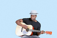 Young African American man playing guitar over light blue background