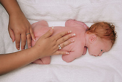 Newborn baby having a body massage,