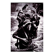 A Nicaraguan Contra fords a river in the northern part of the country near the Honduran border while on patrol with a small group of comrades. Summer of 1987.