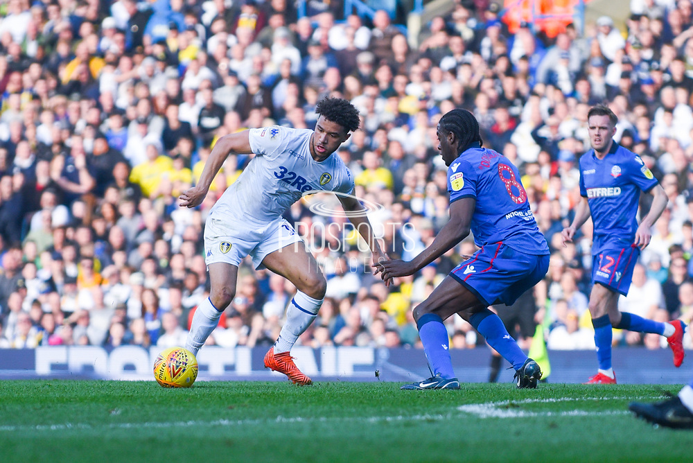 Tyler Roberts of Leeds United (11) takes on Clayton Donaldson of Bolton Wanderers (8) during the EFL Sky Bet Championship match between Leeds United and Bolton Wanderers at Elland Road, Leeds, England on 23 February 2019.