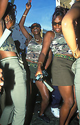 A group of girls matching in camo gear dance at Notting Hill Carnival.