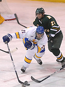 LSSU's Will Acton (21) reaches for the puck after a faceoff with NMU's Andrew Cherniwchan (23) Saturday at Taffy Abel Arena in Sault Ste. Marie.