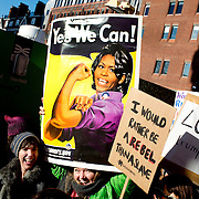London UK. January 21st 2017. One demonstrator holds a picture of Michelle Obama with the caption 'Yes we can' and another has one saying 'I would rather be a rebel than a slave'.  An estimated 100,000 protesters took part in a Women's March from the US Embassy in Grosvenor Square to Trafalgar Square as part of an international campaign on the first full day of Donald Trump's Presidency of the United States.