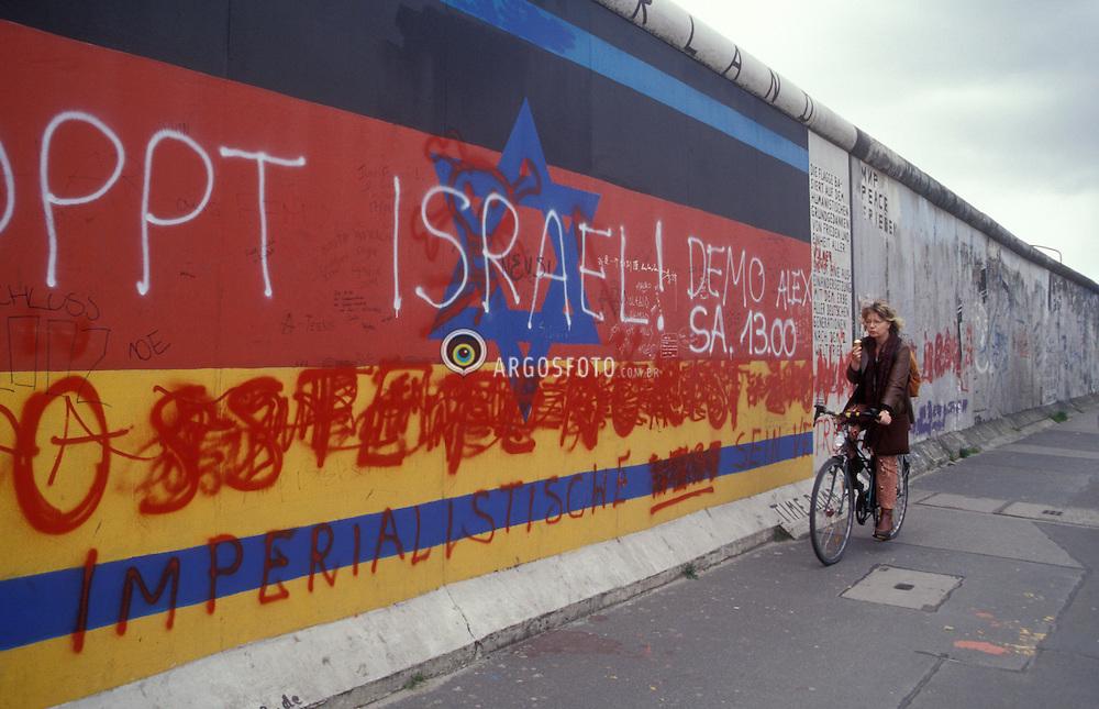 Berlin,Alemanha.abril/2002..Muro de Berlin, parte restaurada, chamada east side.Jovem de bicicleta passa em frente do muro pichado..Foto Adri Felden/Argosfoto