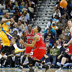 February 12, 2011; New Orleans, LA, USA; New Orleans Hornets point guard Chris Paul (3) passes the ball past Chicago Bulls point guard Derrick Rose (1) during the third quarter at the New Orleans Arena.  The Bulls defeated the Hornets 97-88. Mandatory Credit: Derick E. Hingle
