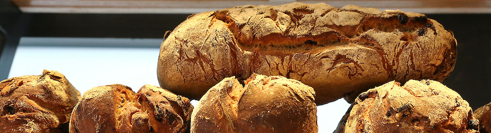 """Freshly baked loaves of bread at a bakery. This image was part of a photo exhibition """"Let there be Bread"""" by Oren Shalev in the Eretz Israel Museum in Tel Aviv, Israel. The motif of the exhibition was bread. Such a basic food yet so complex and diverse. The images were produced by following the nightly work at a bakery from start to finish. To view all images from this exhibition please search for breadexhibition"""