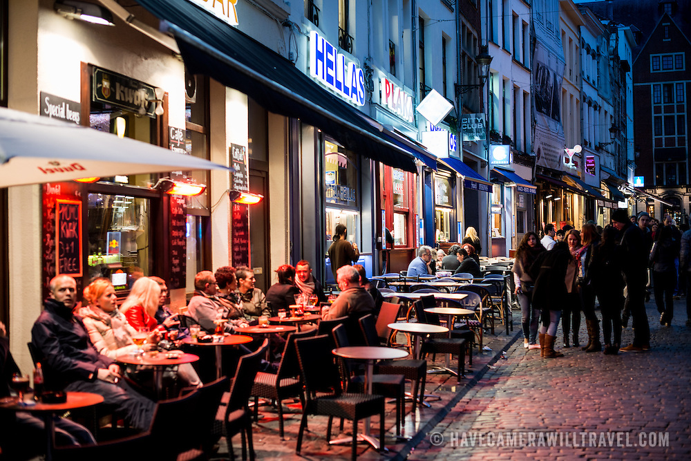 Patrons eat and drink at outdoor seating outside a restaurant in the old town of Brussels, Belgium, at night.