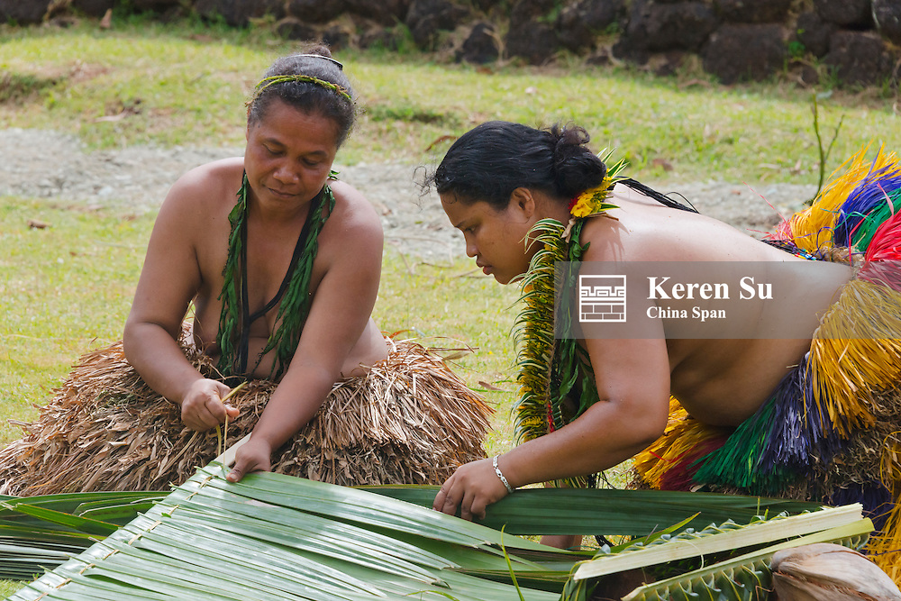 Yapese woman in traditional clothing weaving hand bag with palm tree leaves at Yap Day Festival, Yap Island, Federated States of Micronesia