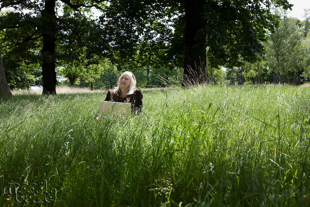 Woman Using a Laptop in a Meadow