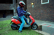 Teenage boy on a scooter moped housing estate Lambeth Walk South London c.2000