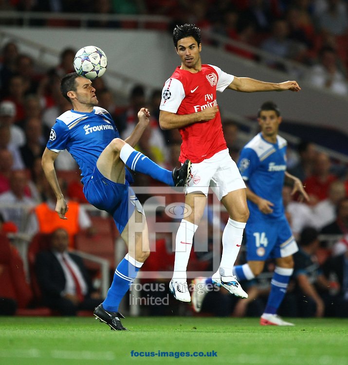 Picture by Paul Chesterton/Focus Images Ltd. 07904 640267.28/9/11.Marouane Chamakh of Arsenal and Pablo Orbaiz of Olympiakos in action during the UEFA Champions League Group F match at The Emirates Stadium, London.