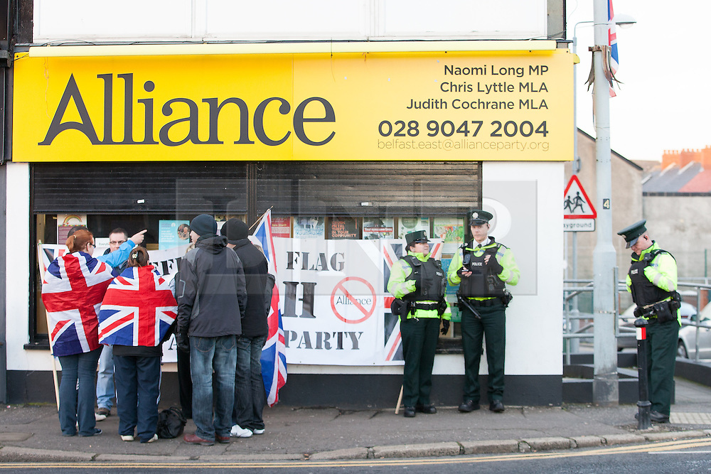 © Licensed to London News Pictures . 09/01/2013 . Belfast , UK . Protesters carrying Union Jack flags congregate outside the office of the Alliance Party on Newtownards Road , East Belfast , today (9th January 2013) . Regular protests have been taking place since the Belfast City Council voted to fly the Union Flag on designated days rather than every day . Photo credit : Joel Goodman/LNP