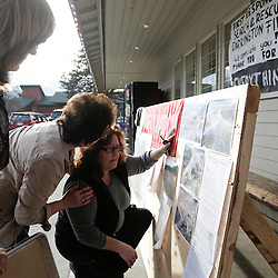 Brenda Neal (R) is consoled by Carol Massingale (2nd L) as she looks at aerial photos of a massive landslide for her missing husband's car in Darrington, Washington March 24, 2014. The confirmed death toll from a devastating weekend mudslide in Washington state climbed to 14 people on Monday as six more bodies were found, while scores of others remained listed as missing two days after the tragedy, authorities said. REUTERS/Jason Redmond (UNITED STATES)