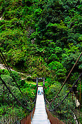 Family crosses a suspended wood foot bridge over the Rio Pastaza in the upper Amazon Basin outside Banos, Ecuador.