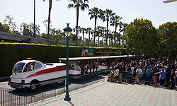 Crowds of people wait in line for a tram to transport them from the parking structure at Disney Land to the theme park.  Disney Land Resort, Anaheim, California, United States of America.