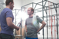 Male friends talking in crossfit gym