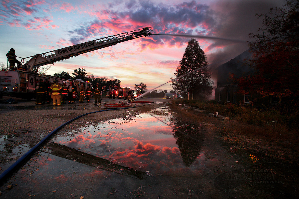 Gary Cosby Jr./Decatur Daily    The Bergen Patterson Warehouse on Court Street in Moulton was heavily damaged by fire late Tuesday afternoon.  Fire departments from across the county assisted Moulton in extinguishing the blaze in the abandoned warehouse.  Firefighters work from the ground and from Courtland's ladder truck as the battle the blaze at sunset.