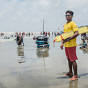 One of the lifeguards of the Life Saving and surfing Club carefully watches the crowded beach of Cox's Bazar, Bangladesh on a busy and sunny Saturday morning