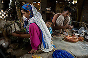 A family is aligning glass bracelets inside their home transformed into a small-scale workshop in the slum surrounding Firozabad, renowned as the 'glass city', in Uttar Pradesh, northern India. Due to extreme poverty, over 20.000 young children are employed to complete the bracelets produced in the industrial units. This area is considered to be one of the highest concentrations of child labour on the planet. Forced to work to support their disadvantaged families, children as young as five are paid between 30-40 Indian Rupees (approx. 0.50 EUR) for eight or more hours of work daily. Most of these children are not able to receive an education and are easily prey of the labour-poverty cycle which has already enslaved their families to a life of exploitation. Children have to sit in crouched positions, use solvents, glues, kerosene and various other dangerous materials while breathing toxic fumes and spending most time of the day in dark, harmful environments. As for India's Child Labour Act of 1986, children under 14 are banned from working in industries deemed 'hazardous' but the rules are widely flouted, and prosecutions, when they happen at all, get bogged down in courts for lengthy periods. A ban on child labour without creating alternative opportunities for the local population is the central problem to the Indian Government's approach to the social issue affecting over 50 million children nationwide.