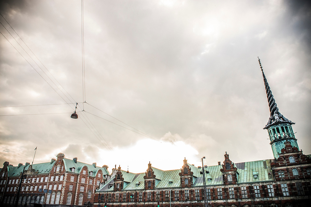 Dark, moody skies gather over Copenhagen's Imposing, 17th-century, waterfront building & former stock exchange, Børsen. It's striking spire contains the image of three dragons with their tails intertwined.