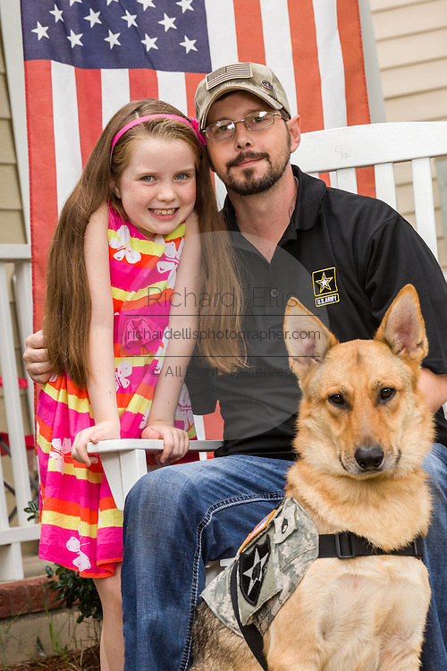 Rachel Mennet, a third-grader, poses with wounded warrior Nick Bailley and his dog Abel on September 23, 2014 in Summerville, South Carolina. Rachel led a successful fundraising effort using her lemonade stand to pay for training Abel to become a service dog for Nick.