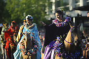 The Kau-Lio Pau Riders of Hawaii wave to the crowd in the 2011 Alaska Airlines Seafair Torchlight Parade in Seattle Saturday, July 30, 2011.<br />