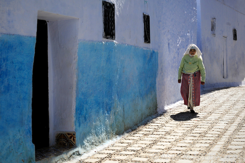 Morocco, Chefchaouen. Woman wearing traditional Rif Mountains dress in the blue street.