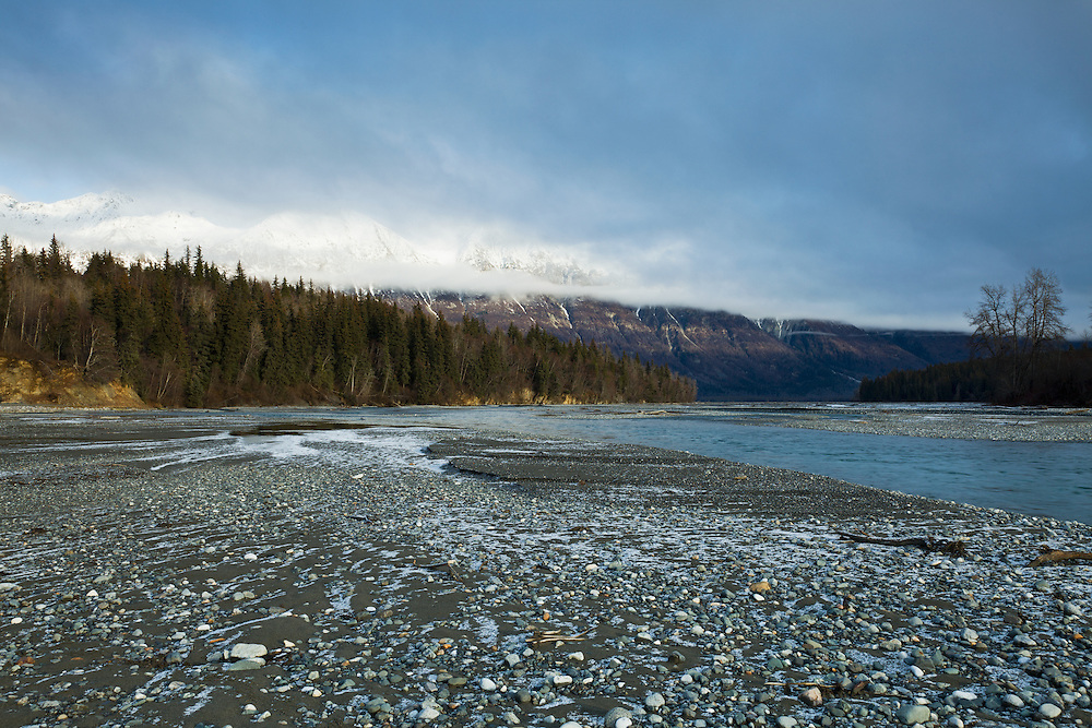 Late afternoon sun illuminates the trees and Takshanuk Mountains along the Chilkat River in the Chilkat Bald Eagle Preserve as a storm system moves in near Haines in Southeast Alaska. Winter. Afternoon.