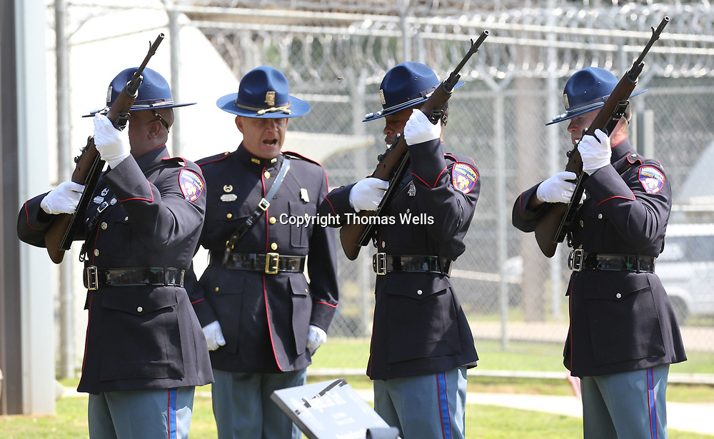 The Mississippi Highway patrol Honor Guard perform the 21 gun salut to conclude the flag dedication service for MBN officer Lee Tartt.