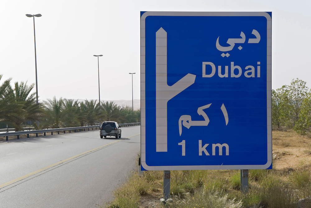 UAE,VAE,Vereinigte Arabische Emirate, Dubai,  Ein Hinweisschild kurz hinter Dubai auf der Autobahn Richtung Al Ain weist auf die Abfahrt Richtung Dubai in einem Kilometer Entfernung hin. | UAE, United Arab Emirates, Dubai,  A sign at the highway -autobahn- motorway- from Dubai to Al Ain hints to the exit for Dubai exit at a distance of one kilometer. |