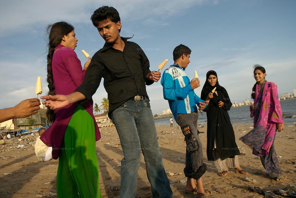 People enjoy Kulfi (a home made ice cream) on Chowpatti beach. Mumbai, June 2007