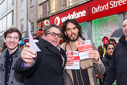 "Oxford Street, London, December 5th 2014. Actor and Comdeian turned political activist Russel Brand visits several big brands'  stores including Boots, Apple and Vodafone in London accusing them of dodging tax whilst those most in need of benefits are facing cuts and increased hardship. A leaflet being distributed by him claims £14 billion is lost every year, through tax avoidance and loopholes exploited by big business. PICTURED: A member of the public poses with Russel Brand and his leaflets that accuse Vodafone of being a ""Tax Dodger""."