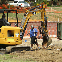 Thomas and Adrian Sanchez, employees with Tupelo Parks and Recreation, work on installing a drainage and irrigation system on the west side of the walking track at Robins Field on Thursday.