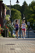 Two friends running through town in the early morning.