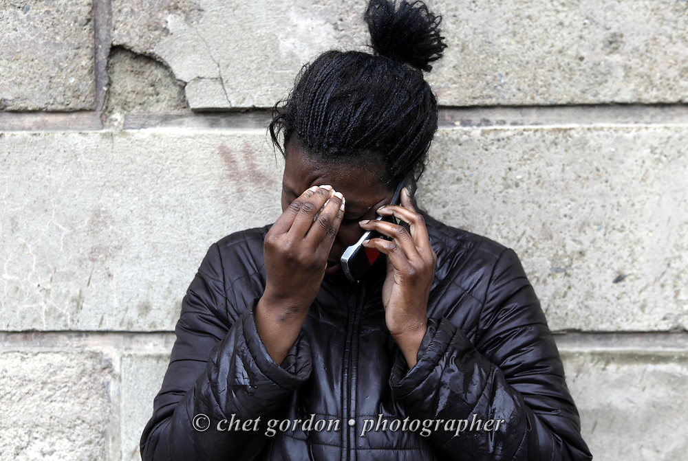 """Shameeka Burks (24) cries as she talks on a cellular telephone near the intersection of Benkard Ave. and Little Monument Street in the City of Newburgh, NY on Saturday morning, March 13, 2010. Her boyfriend, John """"Tarzan"""" Maldonado (21) was shot and killed at the scene on Friday night."""