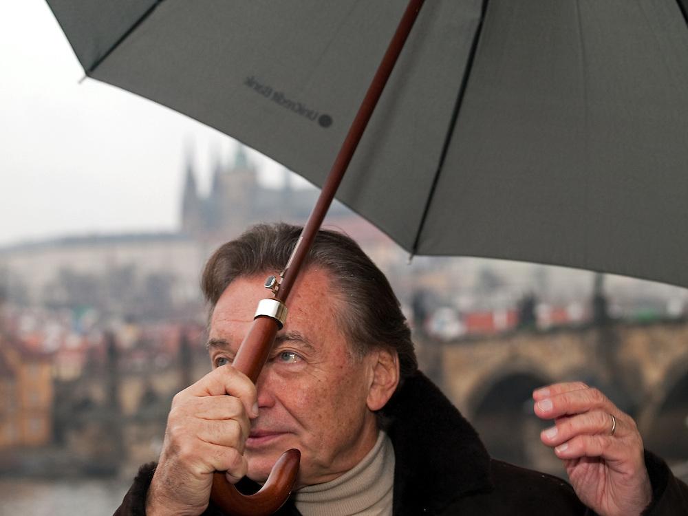10:13 Czech singer Karel Gott covering himself with an umbrella against starting snow close to Pragues Charles Bridge.
