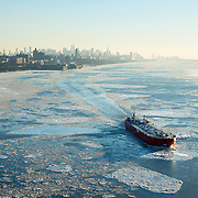 January 30, 2014 - New York, NY : A large ship is pushed by a tug boat up the frozen Hudson River -- breaking ice floes as it goes -- near the George Washington Bridge between New York City and New Jersey, at sunset in January. The New York City skyline can be seen in the distance.  CREDIT: Karsten Moran / Aurora Photos
