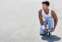 Portrait of young attractive man wearing sports wear tying his rubber shoes in park