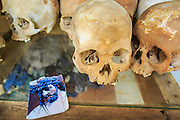 "30 JANUARY 2013 - CHEOUNG EK, CAMBODIA: A picture of Jesus Christ left by a tourist next to human skulls on display in the Buddhist stupa at the Choeung Ek killing fields. Choeung Ek is a former orchard and Chinese cemetery about 17 km south of Phnom Penh, Cambodia. It is the best-known of the ""Killing Fields"", where the Khmer Rouge regime executed over one million people between 1975 and 1979. Mass graves containing 8,895 bodies were discovered at Choeung Ek after the fall of the Khmer Rouge regime. Many of the dead were former political prisoners who were kept by the Khmer Rouge in their Tuol Sleng detention center, a former high school in Phnom Penh.      PHOTO BY JACK KURTZ"