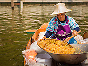 "14 FEBRUARY 2015 - BANGKOK, THAILAND: A vendor makes ""mee krop"" (crispy rice noodles fried in tamarind sauce) at the new floating market opened in Khlong Phadung Krung Kasem, a 5.5 kilometre long canal dug as a moat around Bangkok in the 1850s. The floating market opened at the north end of the canal near Government House, which is the office of the Prime Minister. The floating market was the idea of Thai Prime Minister General Prayuth Chan-ocha. The market will be open until March 1.    PHOTO BY JACK KURTZ"