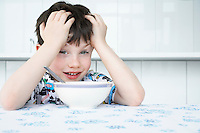 Boy (5-6) sitting at table with bowl in front of face