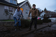 (Gabe Green   The Daily World)<br /> <br /> Nanci Dayton and her son Brayden Dayton, 13, shovel a thick layer of mud, deposited by an overflowing stream, from the sidewalk in front of their house in the Canyon Court neighborhood in Aberdeen Tuesday evening.