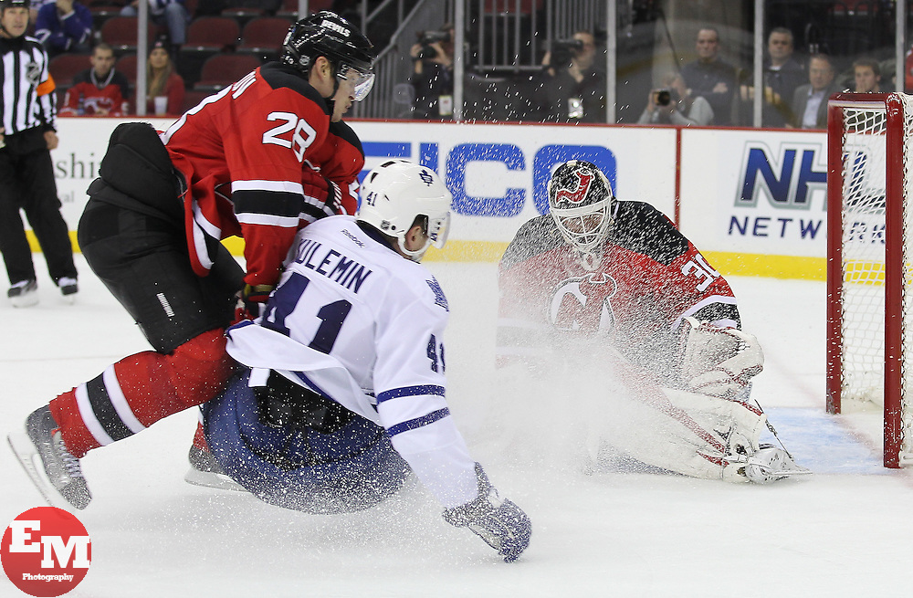 Nov 2; Newark, NJ, USA; New Jersey Devils goalie Martin Brodeur (30) makes a save on Toronto Maple Leafs right wing Nikolai Kulemin (41) while New Jersey Devils defenseman Anton Volchenkov (28) defends during the third period at the Prudential Center. The Maple Leafs defeated the Devils 5-3.