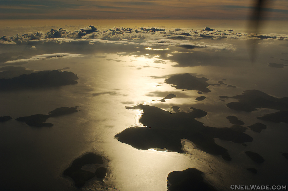 Looking out the airplane window on a small prop plane headed from Manila to Taytay, Palawan, the Philippines.  Below are some remote islands of the Philippine archipelago.